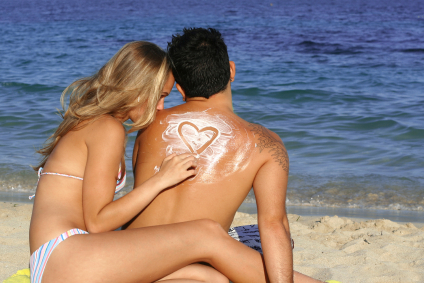Honeymoon couple on the beach drawing a sunscreen heart for marriage rules joke