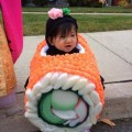 A little girl is dressed up as a sushi roll for Halloween. Hilarious!